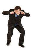 Businessman ducking in fear and closing ears. Young businessman ducking in fear and closing ears with fingers isolated on white Royalty Free Stock Image