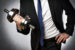 Businessman with dumbbell. Image of a businessman with dark suit and silver dumbbell royalty free stock images