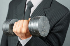 Businessman with dumbbell Stock Photography