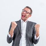 Businessman with dynamic body language screaming victory. Conviction concept - ecstatic middle aged businessman with dynamic body language screaming his victory Stock Photos