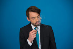 Businessman with e-cigarette wearing suit and tie on blue Royalty Free Stock Photos