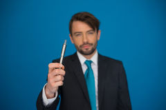 Businessman with e-cigarette wearing suit and tie on blue Stock Photography