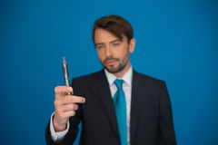 Businessman with e-cigarette wearing suit and tie on blue Stock Image