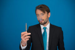 Businessman with e-cigarette wearing suit and tie on blue Stock Photos