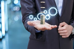 Businessman earns coins through the mechanism. Symbolizes the effective management or production Royalty Free Stock Images
