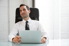 Businessman with earphones and laptop computer Stock Photos