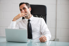 Businessman with earphones and laptop computer Royalty Free Stock Photo
