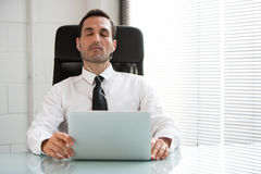 Businessman with earphones and laptop computer Stock Photography