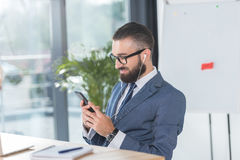 Businessman in earphones using smartphone while sitting at workplace Royalty Free Stock Photo