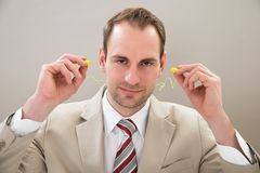 Businessman with earplug Royalty Free Stock Photo