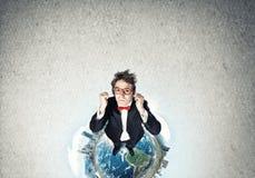Businessman on Earth globe Stock Image