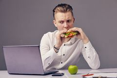Man eat hamburger in office while watch video on his laptop. Businessman eat hamburger in office while watch video on his laptop Royalty Free Stock Photography
