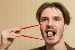 Businessman eat sushi with chopsticks. Stock Photography