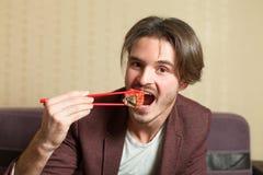 Businessman eat sushi with chopsticks. Royalty Free Stock Photo