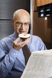 Businessman eating bagel Stock Photography