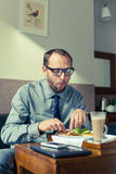 Businessman eating breakfast at home/hotel. Indoor photo. Businessman eating breakfast at home/hotel. Indoor photo Stock Image