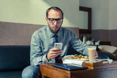 Businessman eating breakfast at home/hotel. Indoor photo. Royalty Free Stock Photo