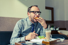 Businessman eating breakfast at home/hotel. Indoor photo. Businessman eating breakfast at home/hotel. Indoor photo Stock Photography