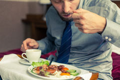 Businessman eating breakfast at home/hotel. Indoor photo. Stock Image