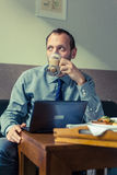 Businessman eating breakfast at home/hotel. Indoor photo. He is. Working on laptop pc Royalty Free Stock Photos