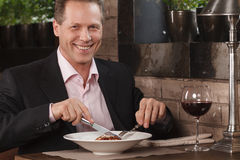 Businessman eating. Confident men in formal wear eating at the r Royalty Free Stock Photo