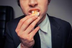 Businessman eating egg Stock Photography