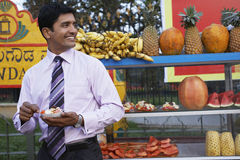 Businessman Eating Fruit Salad At Outdoor Stall Royalty Free Stock Photography