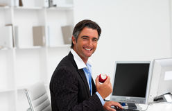 Businessman eating a fruit at work Royalty Free Stock Images