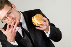 Businessman eating hamburger Stock Photography