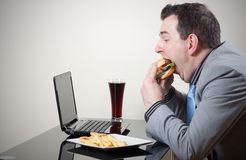 Businessman eating junk food while working Stock Image