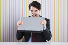 Businessman eating laptop Stock Photography