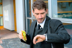 Businessman is eating and looking for time Stock Image