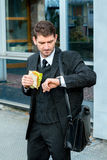 Businessman is eating and looking for time Royalty Free Stock Image