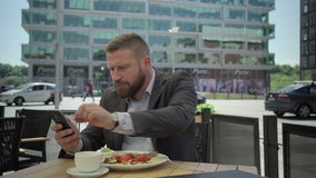Businessman eating lunch and browsing smartphone, steadicam. stock footage