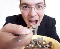 Businessman eating money Stock Images