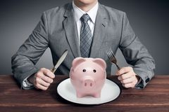Businessman eating piggy bank. Business concept. Businessman eating piggy bank. Piggy bank on the plate. Business concept royalty free stock photography
