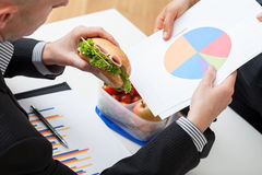 Businessman eating sandwich during work Stock Photography