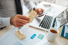 Businessman eating a snack Stock Photography