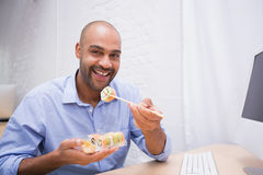 Businessman eating sushi at office desk Royalty Free Stock Photography