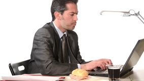 Businessman eating unhealthy food stock video