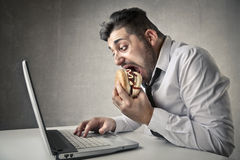 Businessman eating and working Stock Images