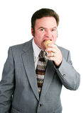 Businessman Eats Chocolate Ice Cream Cone. Handsome man in business suit eating a chocolate ice cream waffle cone. Isolated on white royalty free stock photos