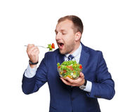 Businessman eats fresh vegetable salad isolated on white Royalty Free Stock Photo