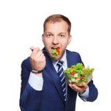 Businessman eats fresh vegetable salad isolated on white Stock Image