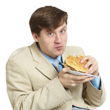 Businessman eats a sandwich isolated on a white Royalty Free Stock Photos