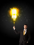 Businessman with an eco-friendly bulb. Businessman hold a shining eco-friendly idea bulb on a black background Royalty Free Stock Photo