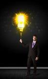 Businessman with an eco-friendly bulb. Businessman hold a shining eco-friendly idea bulb on a black background Stock Photos