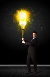 Businessman with an eco-friendly bulb. Businessman hold a shining eco-friendly idea bulb on a black background Royalty Free Stock Photos
