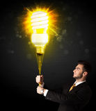 Businessman with an eco-friendly bulb. Businessman hold a shining eco-friendly idea bulb on a black background Stock Photography