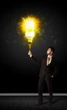 Businessman with an eco-friendly bulb. Businessman hold a shining eco-friendly idea bulb on a black background Stock Photo